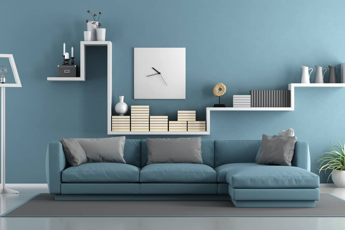 A blue colored wall with an abstract designed cabinet and blue couch