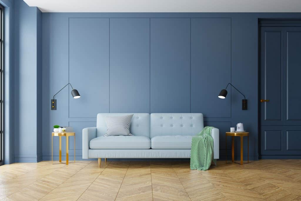 A blue colored wall with sky blue colored couch