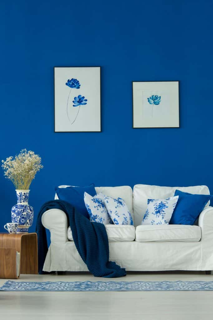 A blue colored wall with two picture frames on the wall and a white couch and floral throw pillows