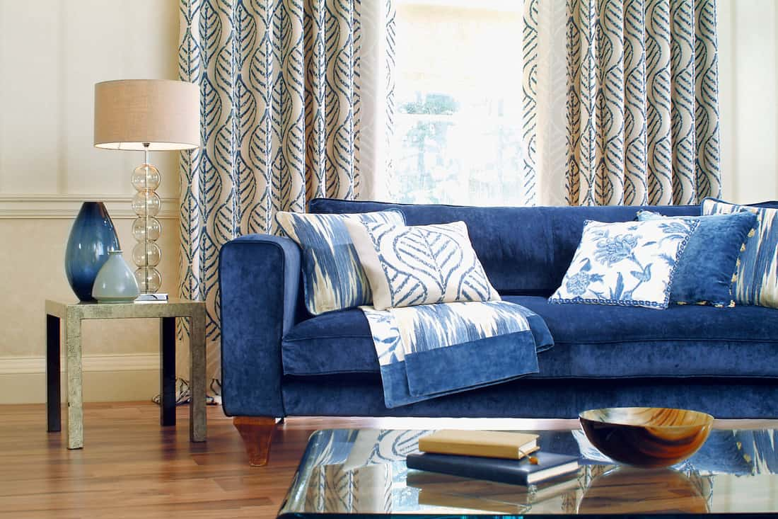 A blue couch placed near the window with floral pattern curtains