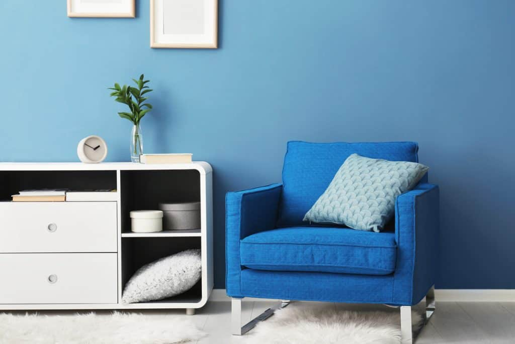 A blue couch with a white cabinet and a blue colored wall