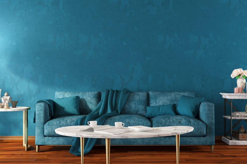A blue couch with blue throw pillows and blue colored wall