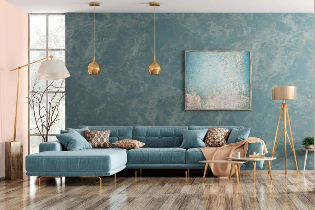 A blue themed living room with a blue sectional couch with gold hanging lamps