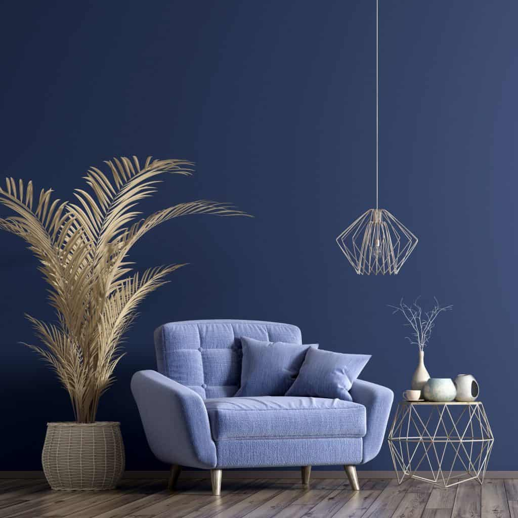 A blue themed living room with a blue sofa and a brown indoor palm tree