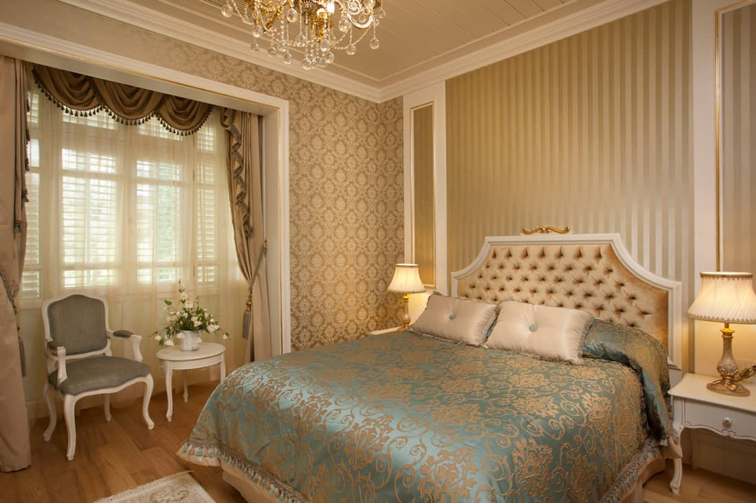 A classic style bedroom with beige colored walls and curtains
