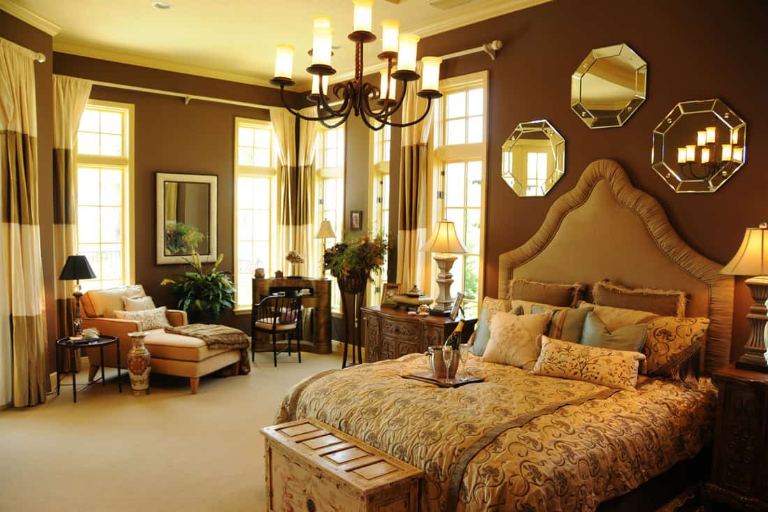 A classic themed bedroom with brown colored walls and a striped patterned curtains