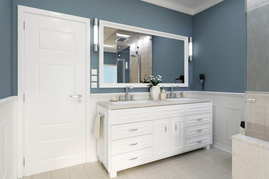 A dark blue colored bathroom with a white colored door and cabinet