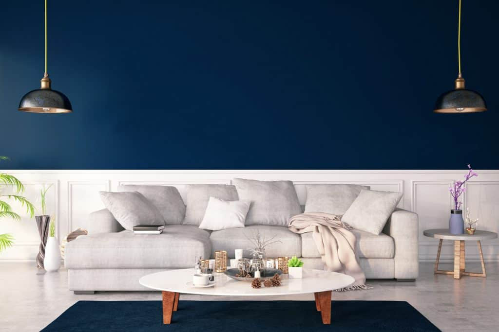 A dark blue colored living room with a white flooring and a tall white baseboard