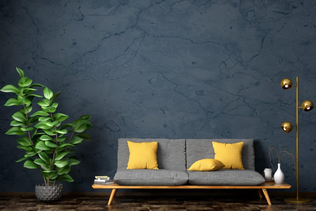 A dark blue colored wall with a gray couch and a gold colored standing lamp
