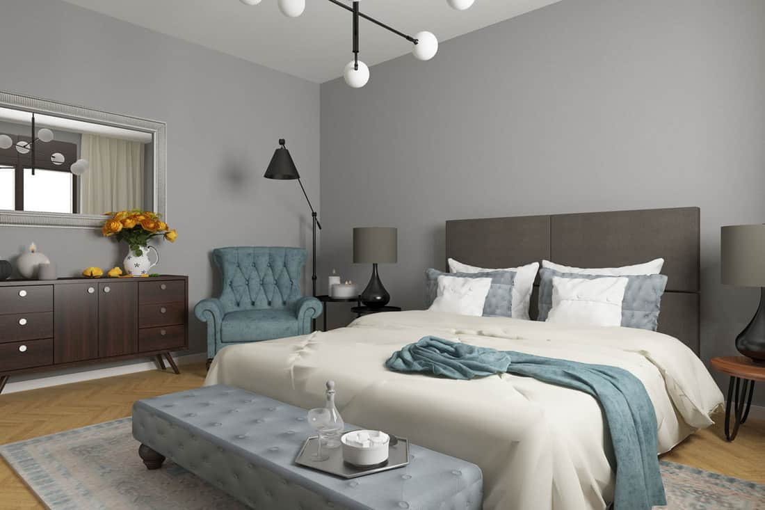 A gray bedroom with brown shelves on the side and an off white blanket