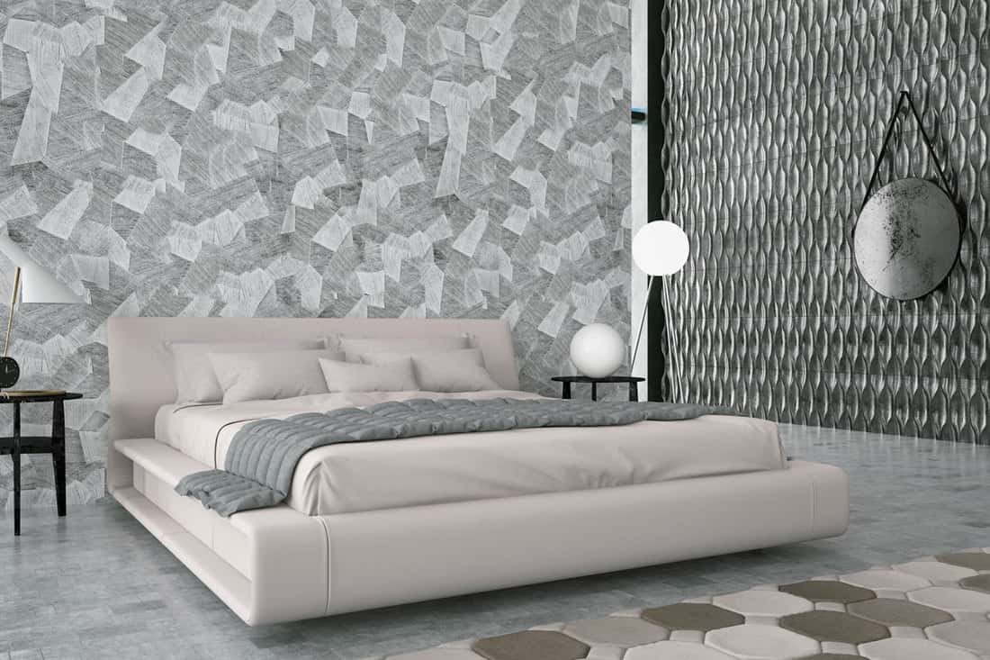 A gray colored bedroom with an off white bed