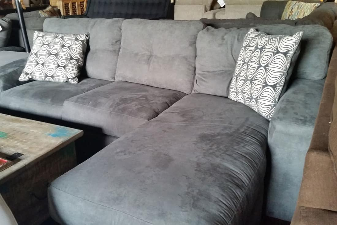 A gray sectional sofa with a throw pillow