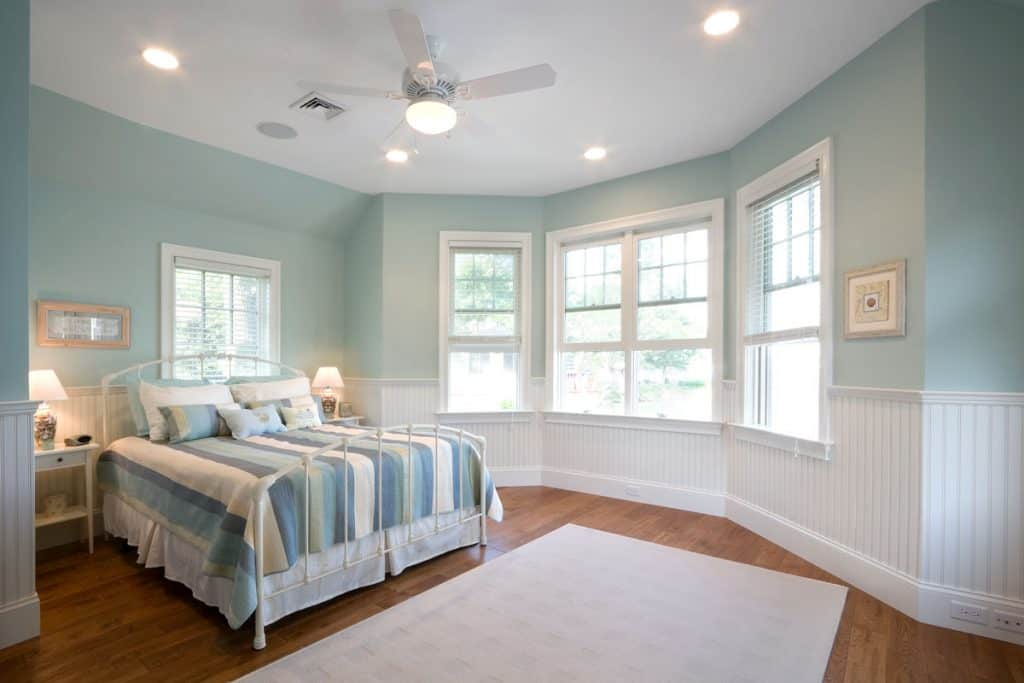 A light blue colored bedroom with a wooden flooring and a white rug