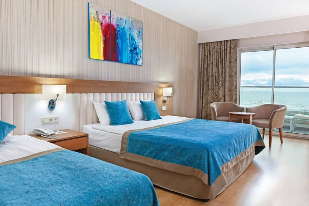 A light brown colored two bedroom unit apartment with blue blankets and blue pillows with a huge window