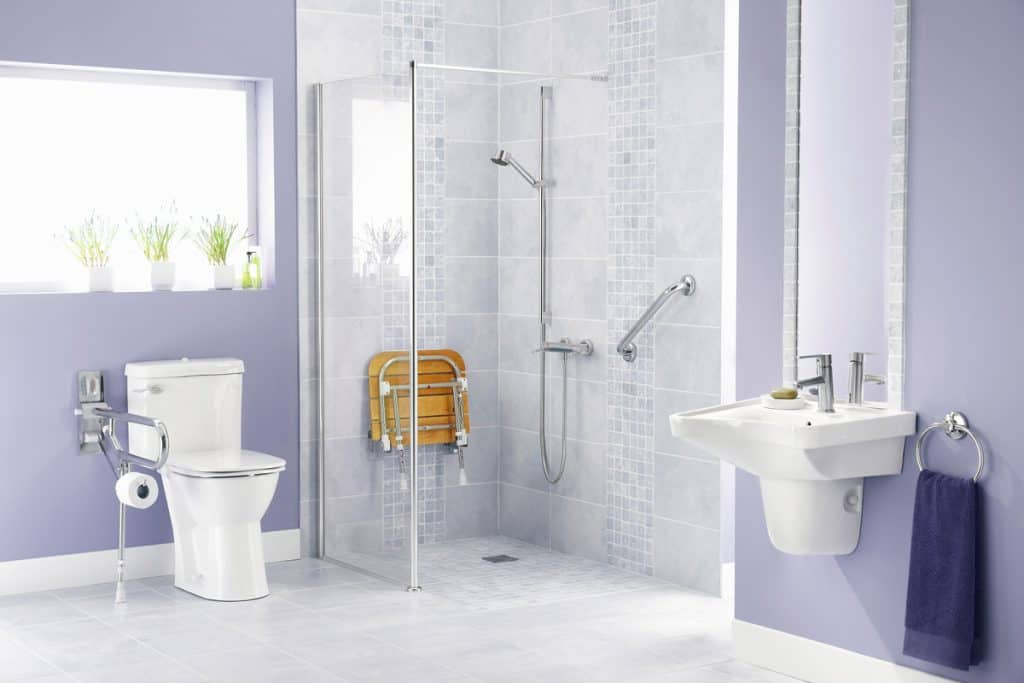 A light colored violet bathroom with and indoor plants on the window