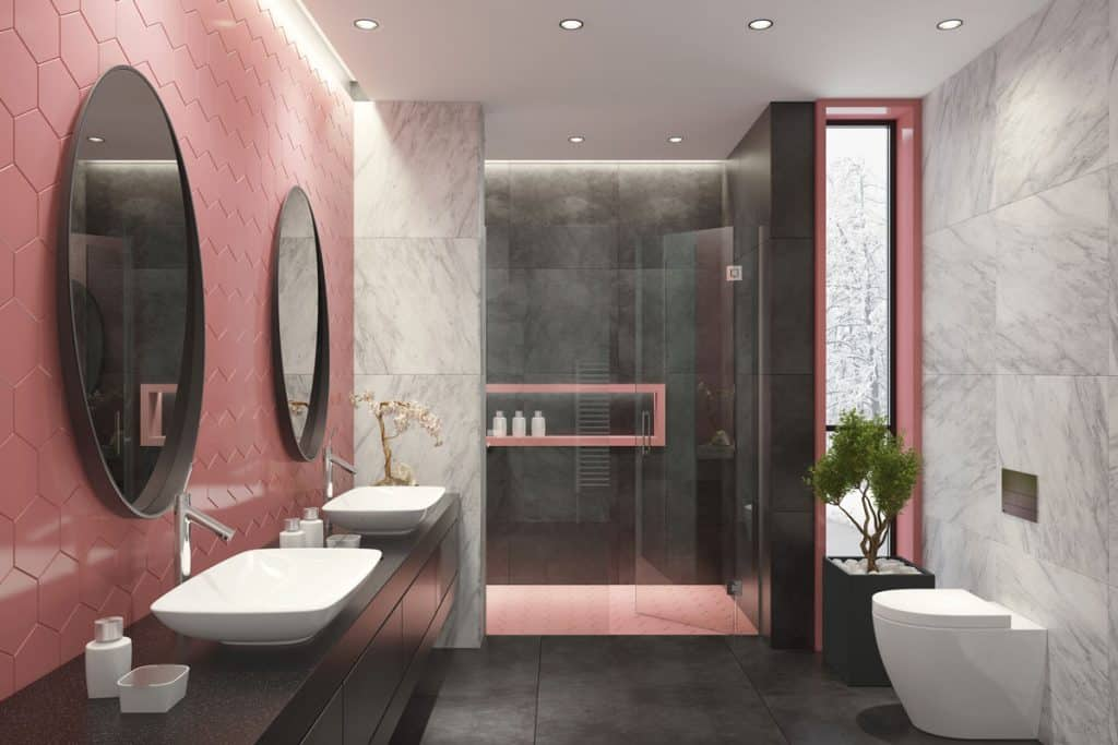 A light pink colored modern bathroom with two huge circular mirror