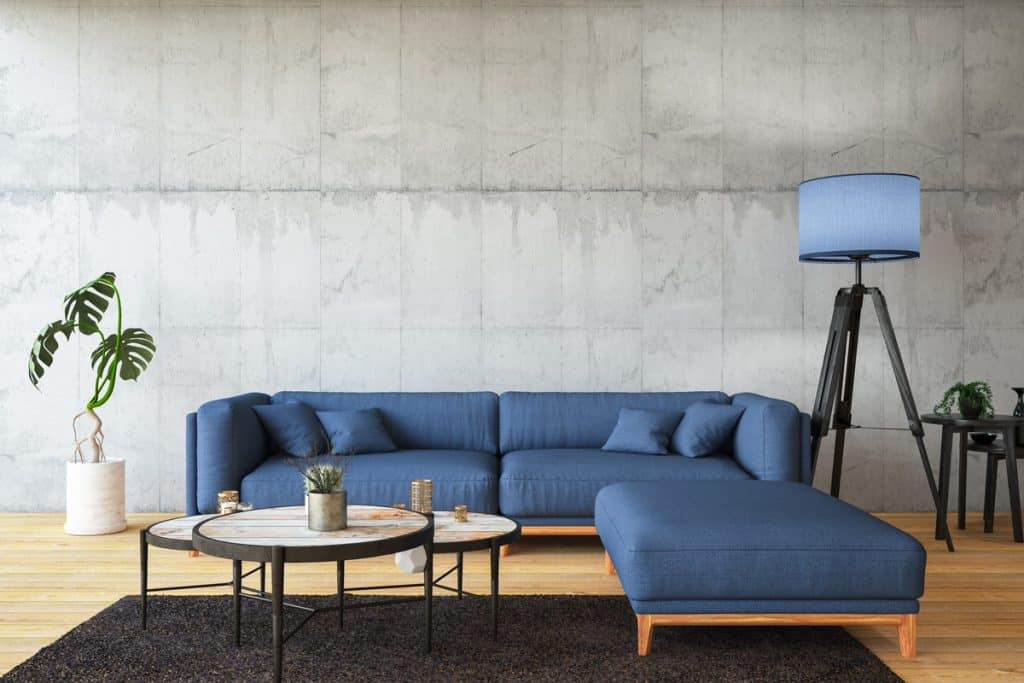 A living room with gray colored walls and a blue colored couch