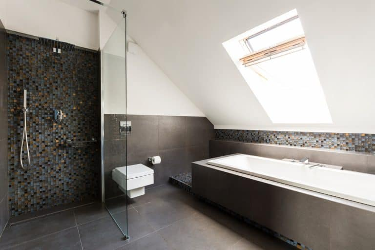 A luxurious living room with an angled ceiling and a dark flooring, What is the Best Flooring for a Small Bathroom? [6 Great Options!]