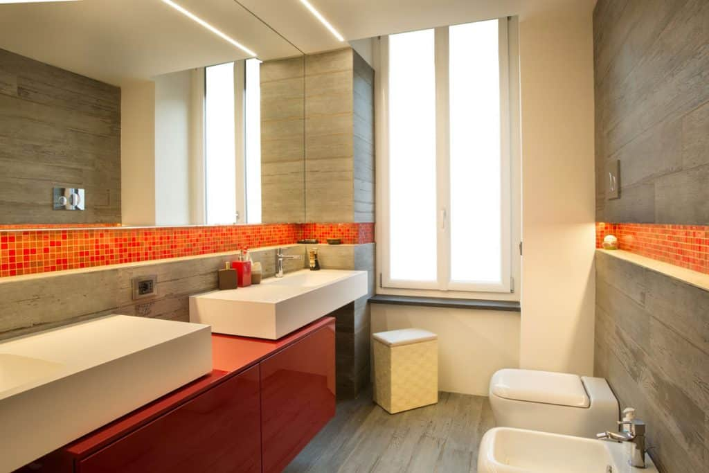 A modern bathroom with an orange outline and an orange cabinet