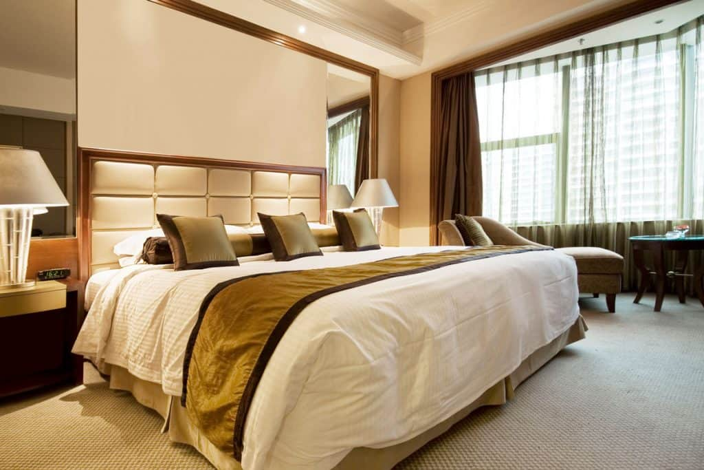 A modern bedroom with a brown curtain, tanned walls, and a bedroom with beautiful pillows