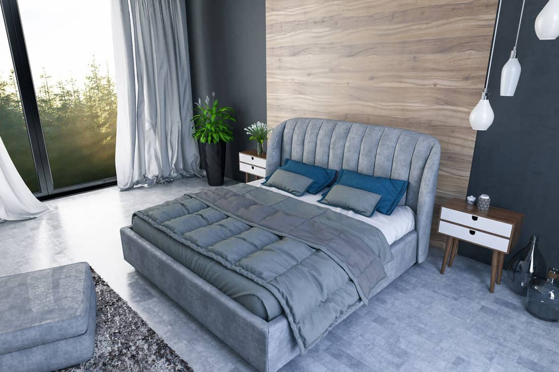 A modern bedroom with a gray bed and a wooden headboard and a huge window on the side