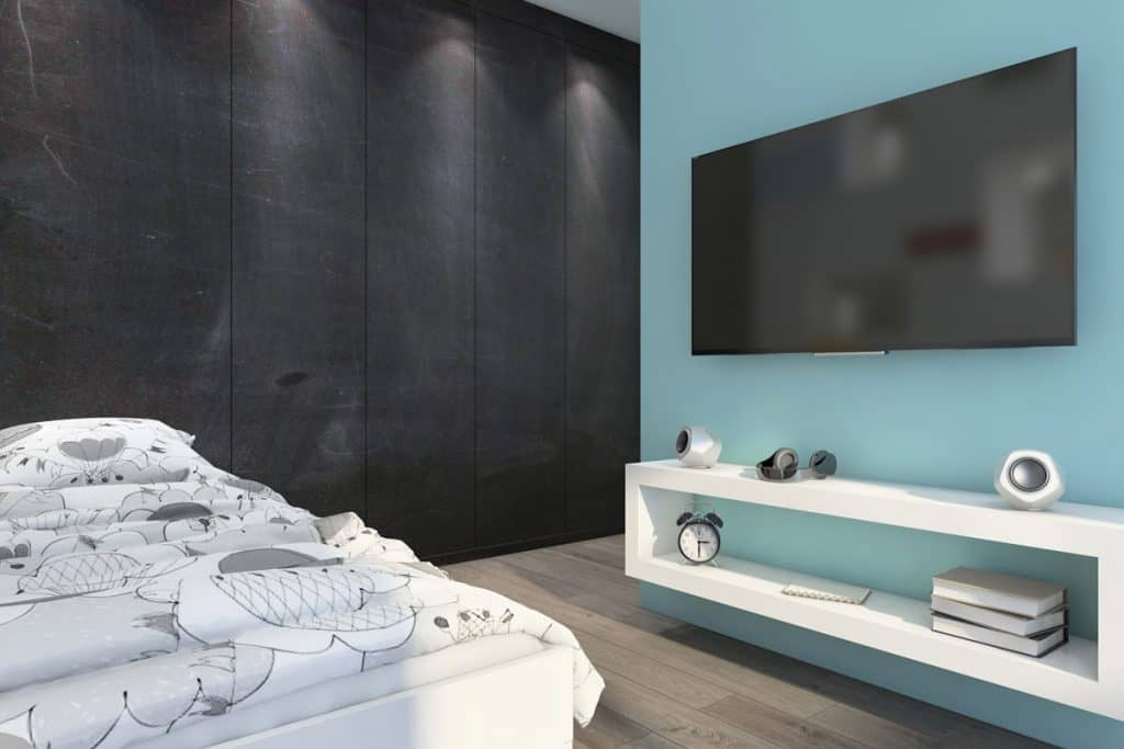 A modern bedroom with a light blue colored wall and a gray wall on the background