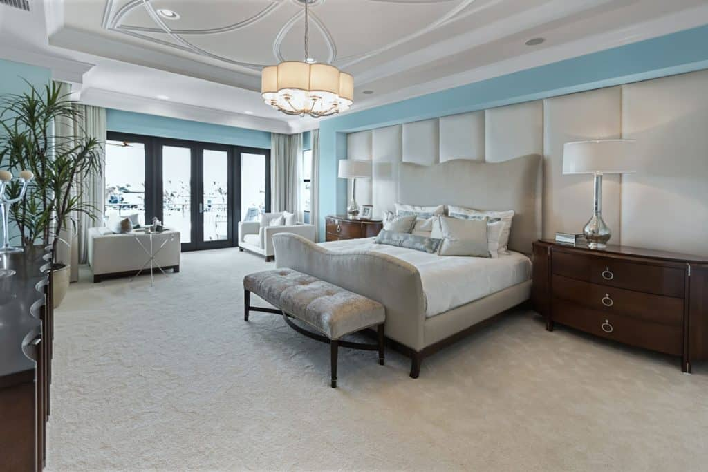 A modern bedroom with a luxurious bed with a light gray colored flooring