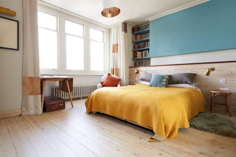A modern masters bedroom with a wooden flooring, yellow blanket, a bookshelf on the side, and three cottage windows, 15 Master Bedroom Bedding Sets Ideas