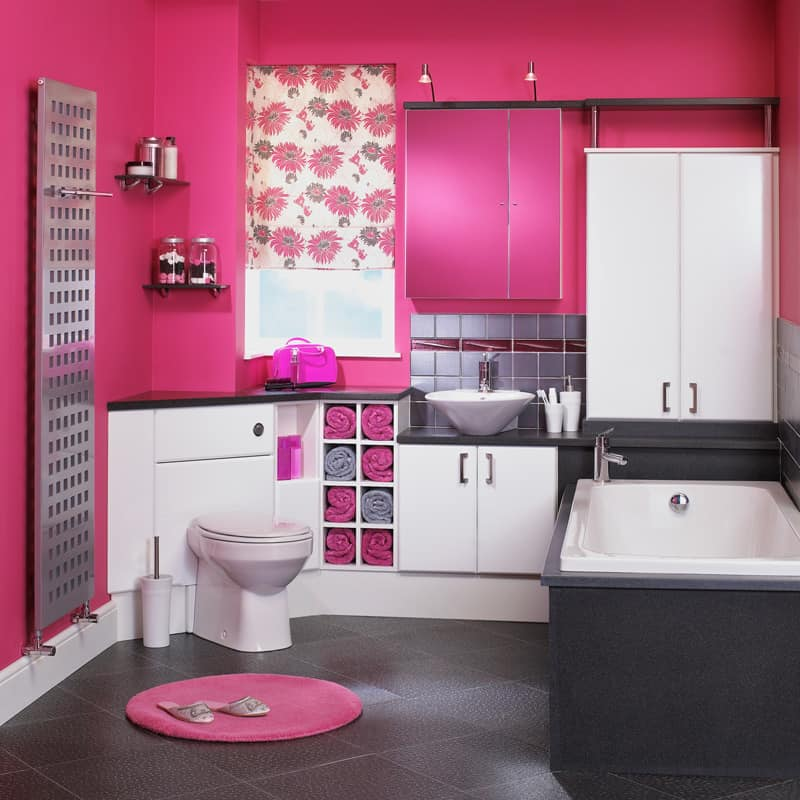 A pink colored bathroom with a bathtub on the side and a corner toilet