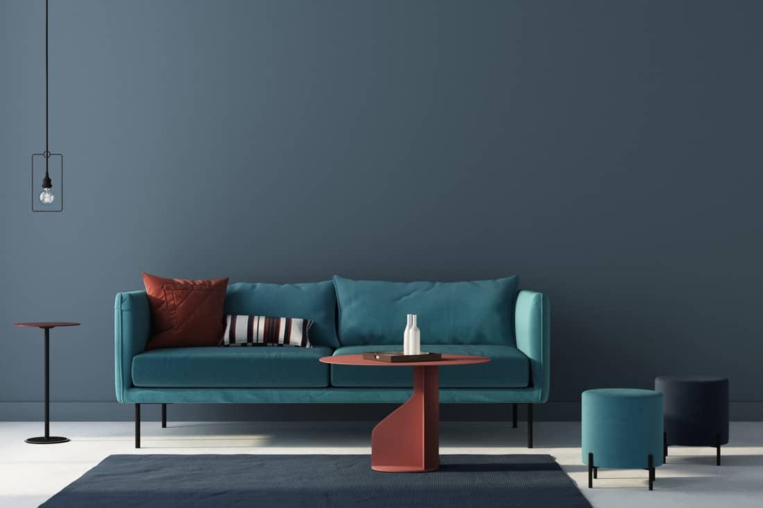A sky blue colored sofa placed near a blue wall