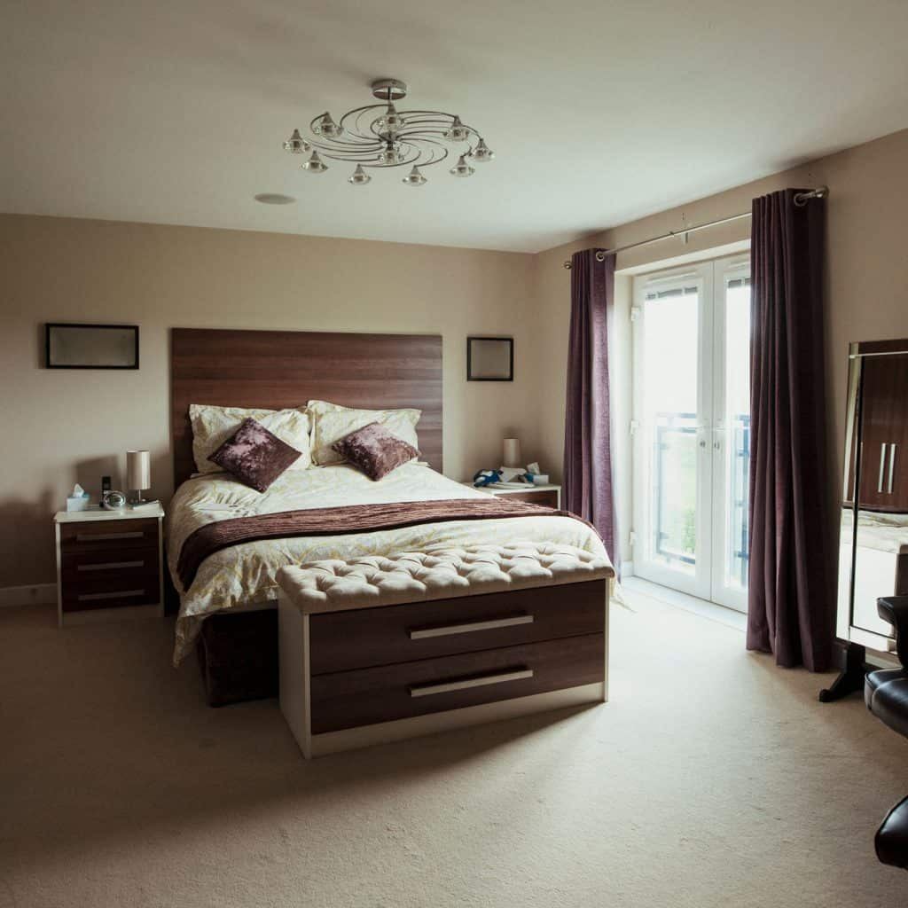 A tanned colored wall and a dark brown colored curtain with a a luxurious bedding set