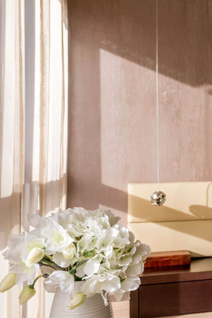 A tanned colored wall with a white colored curtain and a vase with plants