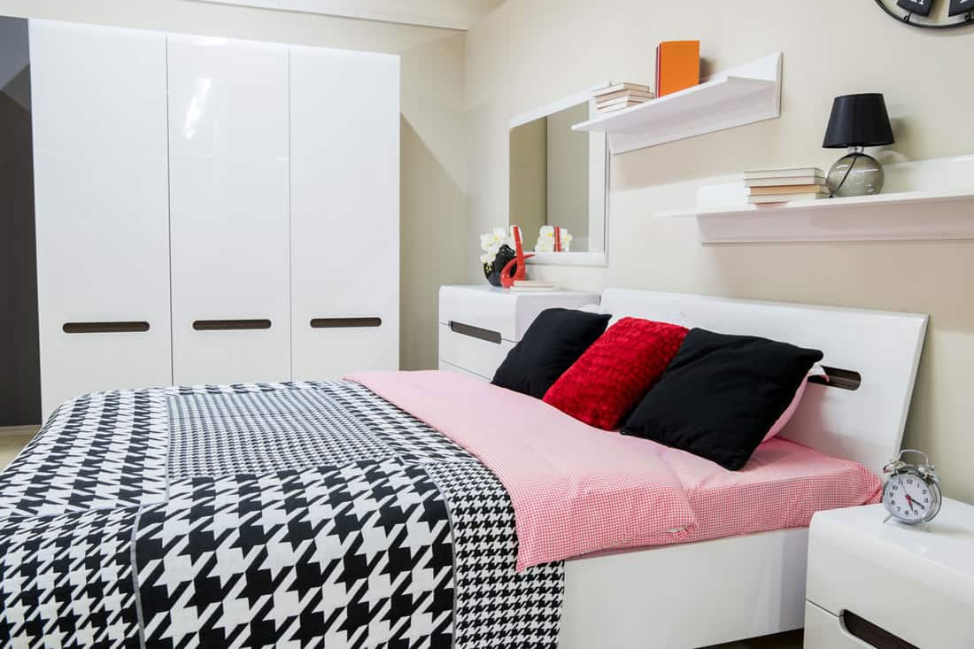 A teens bedroom with a black and white blankets, and a white cabinet