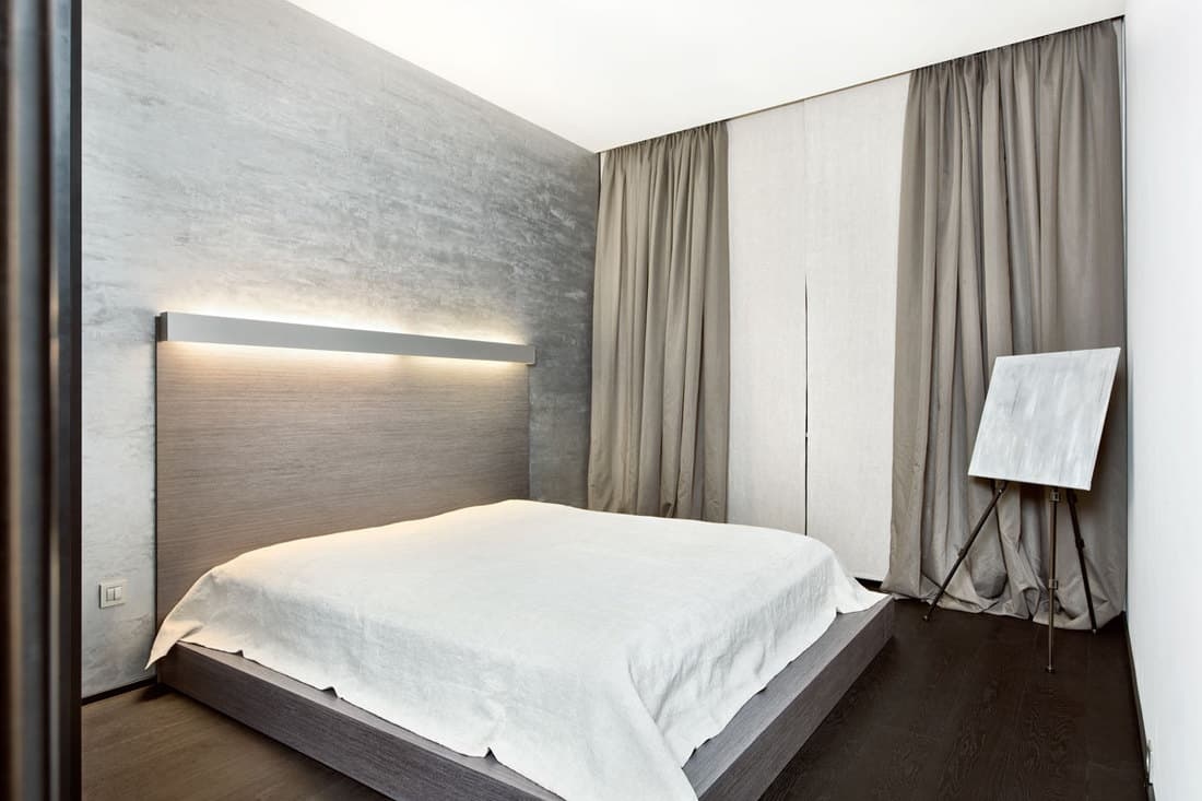 A white bed with a huge curtain covering huge window and a gray textured wall