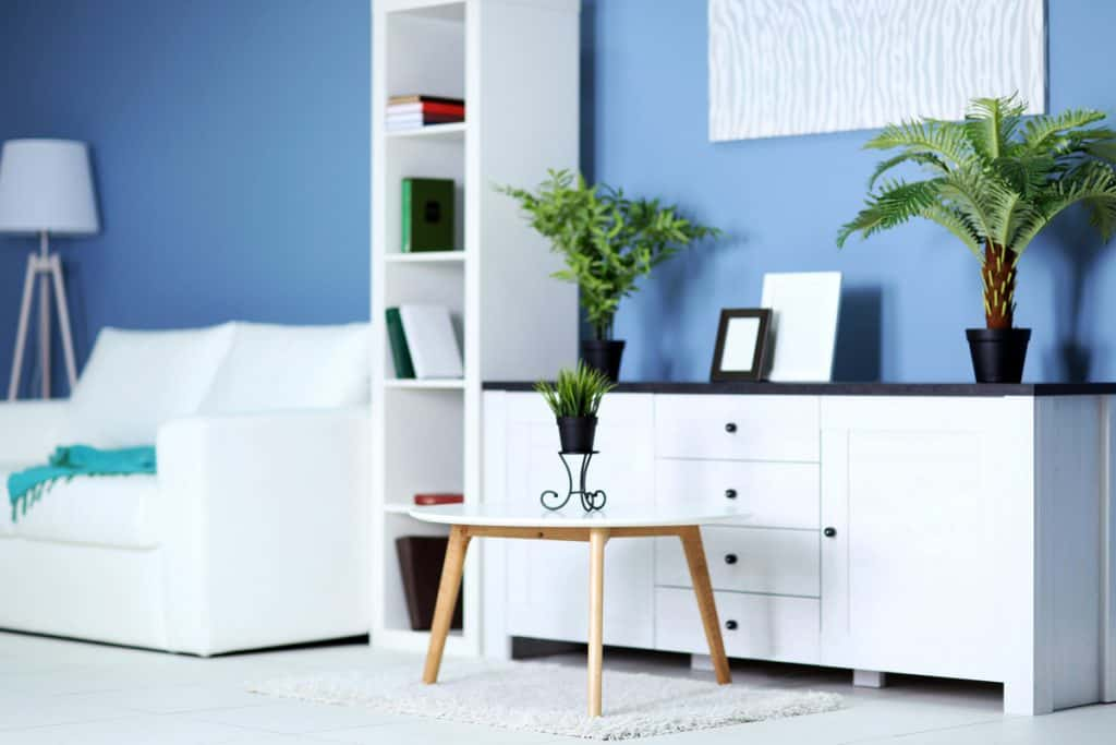 A white cabinet and divider with a blue colored wall living room