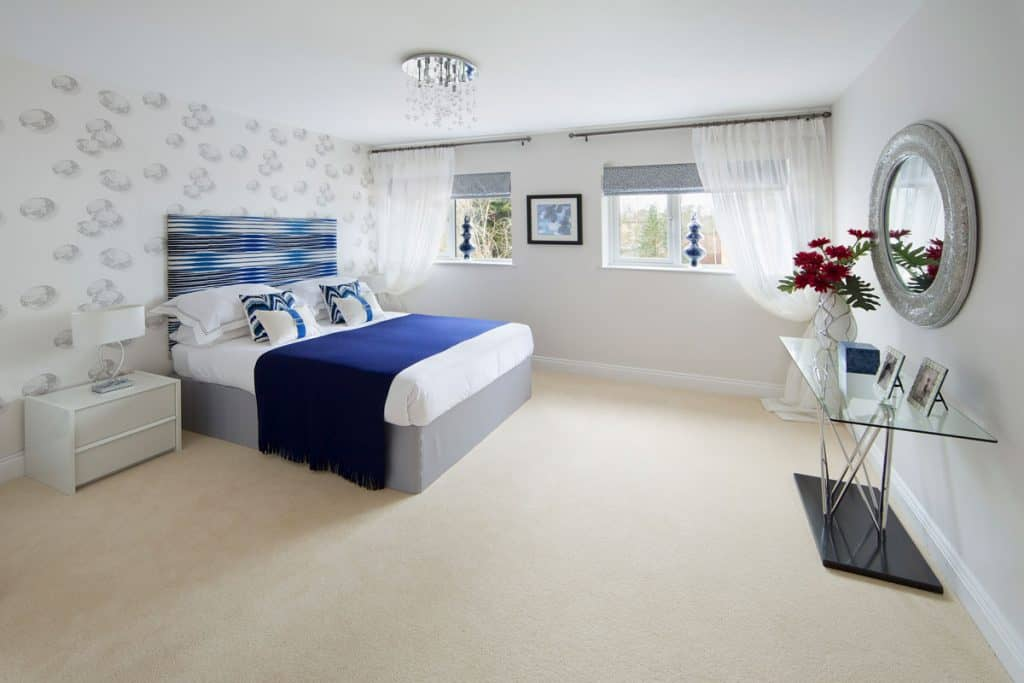 A white colored bedroom with a blue and gray bed