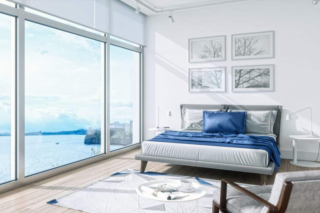 A white colored bedroom with a huge window on the side and a bed with a blue blanket