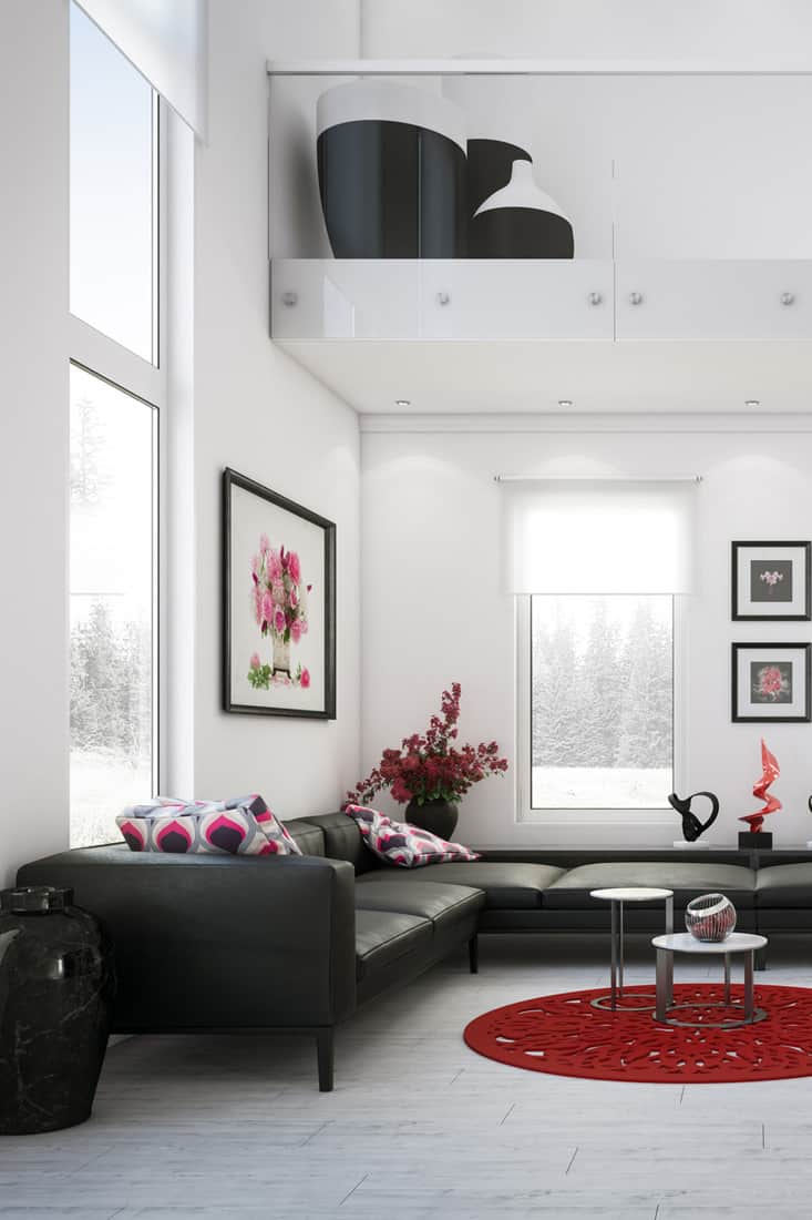 A white colored living room with a black couch and two floral throw pillows