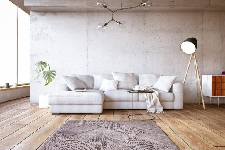 A white couch with white throw pillows and a brown rug on a wooden floor, What Color Rug Goes With White Couch in the Living Room?