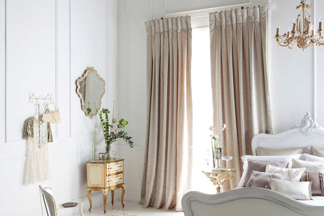 A woman's bedroom with beige colored curtains and white walls