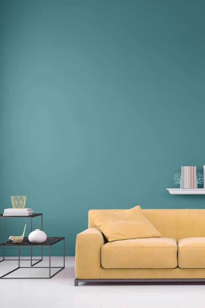 A yellow couch inside an opaque colored blue colored living room