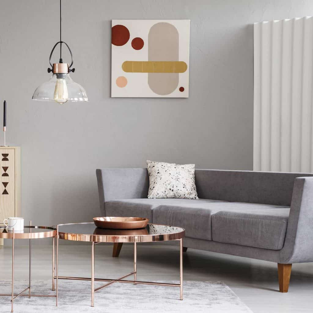 Abstract paintings on a grey wall of a classy living room interior with shiny golden coffee tables