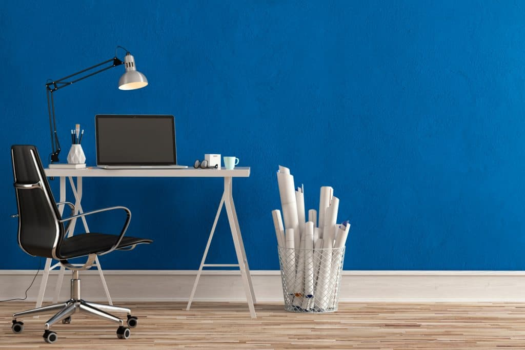An Architects desk with a blue colored wall and wooden flooring