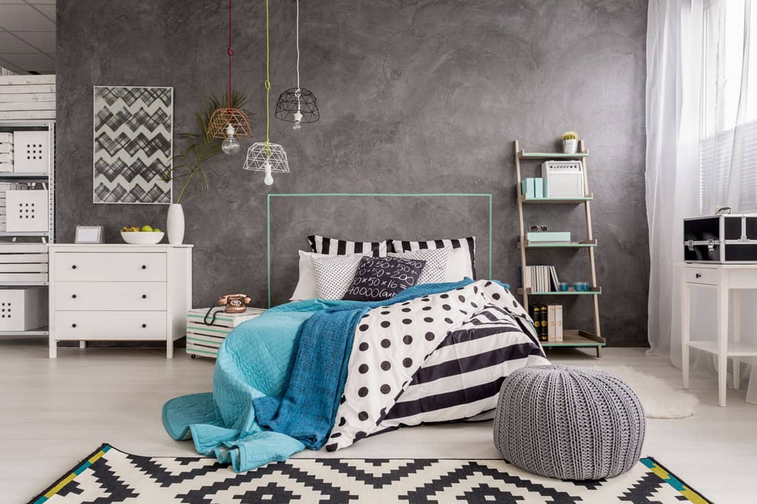 An industrial themed bedroom with a gray wall and stripped rug