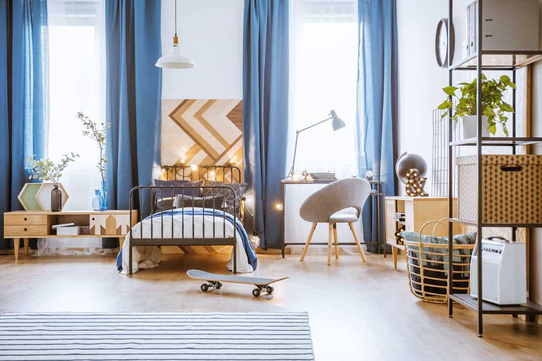 An industrial themed living room with white walls and a blue colored curtain
