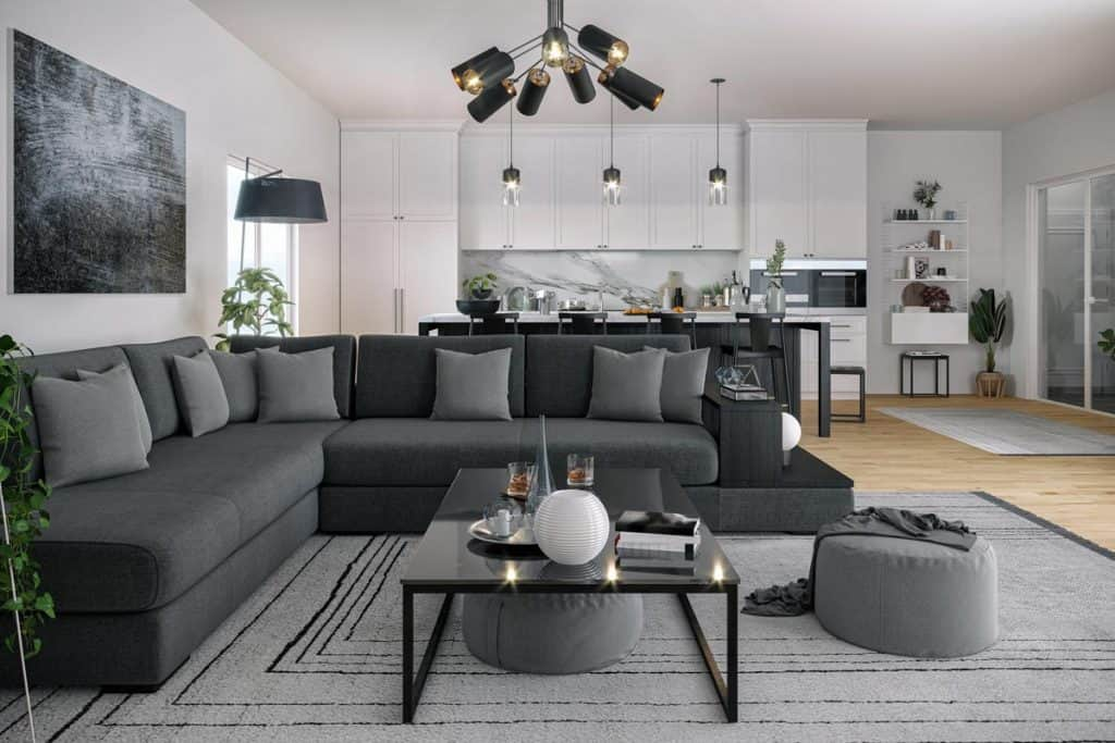 An open space living room with a gray sectional couch and white walls