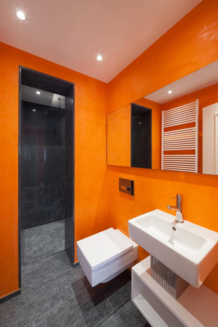 An orange colored bathroom with a square shaped toilet and lavatory