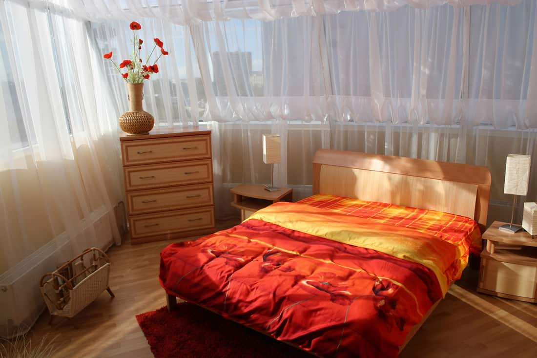 An orange colored bed with white see-through curtains surrounding the bedroom