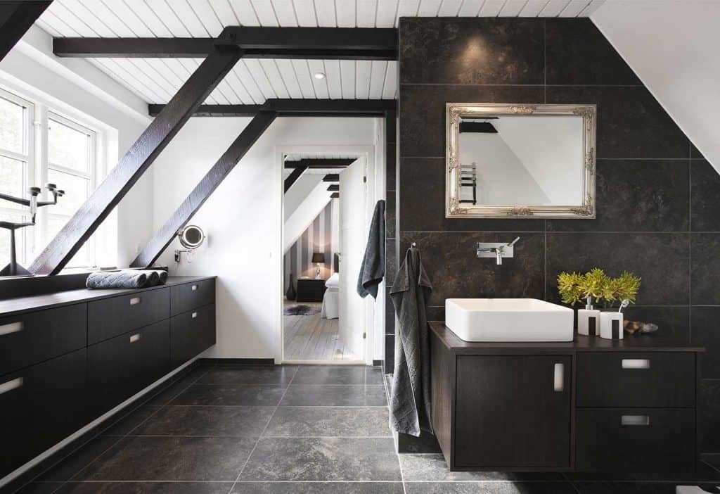Bathroom in conjunction with bedroom with structural beams, dark wood and granite tiles