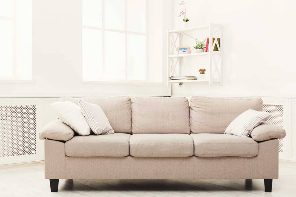 Beige couch with pillows in white modern interior